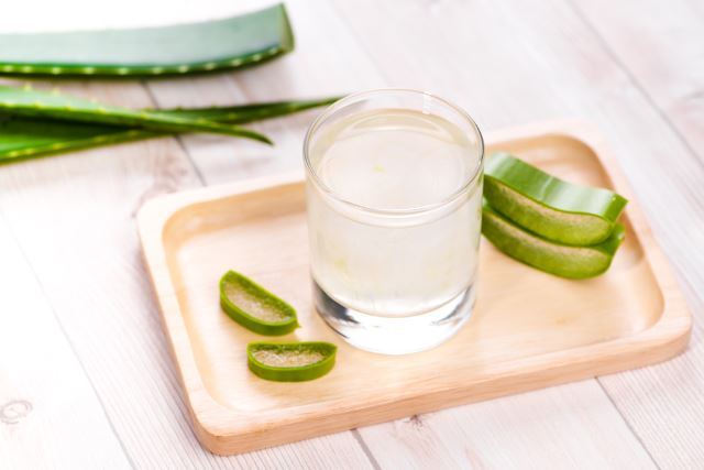 Glass of aloe vera juice with fresh leaves on a wooden table