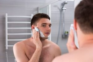 Guy smearing shaving gel on his face in the bathroom