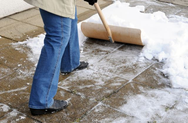 Frau beim Schneeschaufeln / Woman is shovelling snow