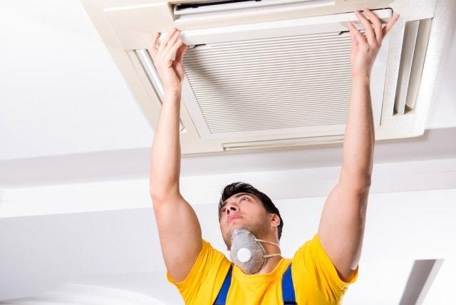 Repairman repairing ceiling air conditioning unit