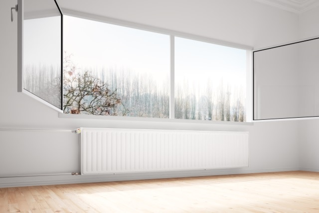 Central heating attachted to wall with open windows