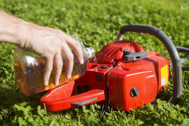Handyman replenishes the oil in chainsaw for chain maintenance