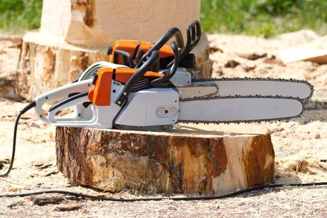 Orange chainsaws standing on a tree stump