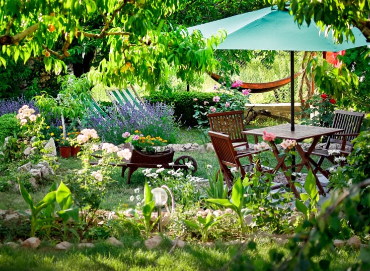 Garden in a lush green and purple flowers sorrounded a table and chairs with green umbrella on it.