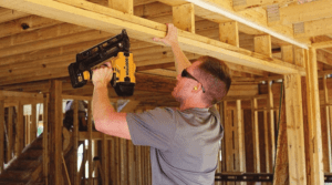 Man Using a Bostitch Cordless Nail Gun to Install the Wood Frame