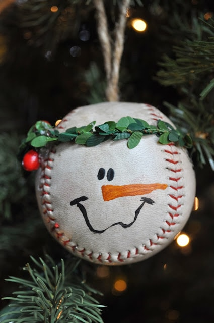 Baseball ball decorated with leaves and drawn eyes, nose and smile to show a snowman face