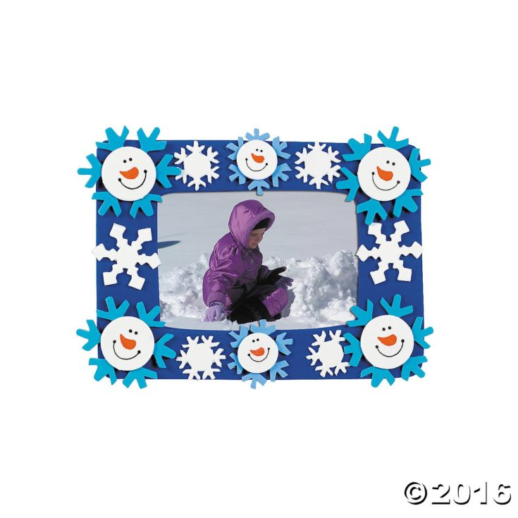 A picture of a child in purple winter coat framed by snowman head and blue and white snowflake