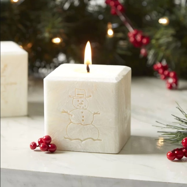 White lit candle with carved snowman in its body