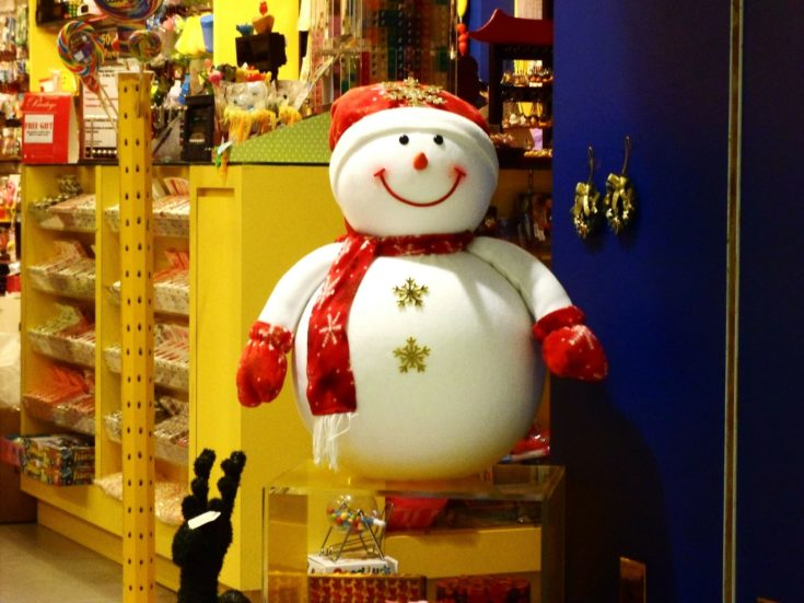 Big Snowman placed in an entrance with several for sale items in the background