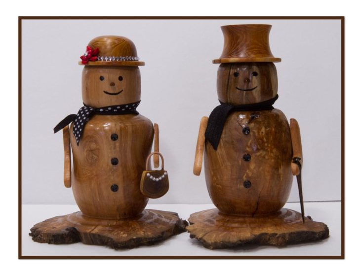 Female and Male wood-carved snowman adorned with cloth as scarf and several little shiny objects