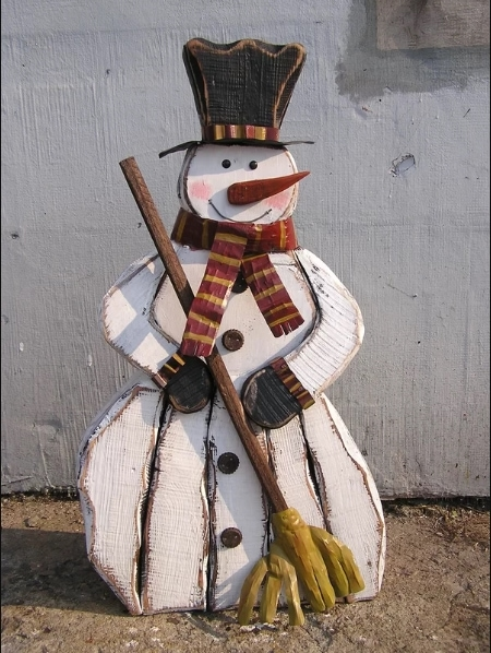 Big snowman designed with eyes, nose and smile with hat and holding made up brooms placed outside