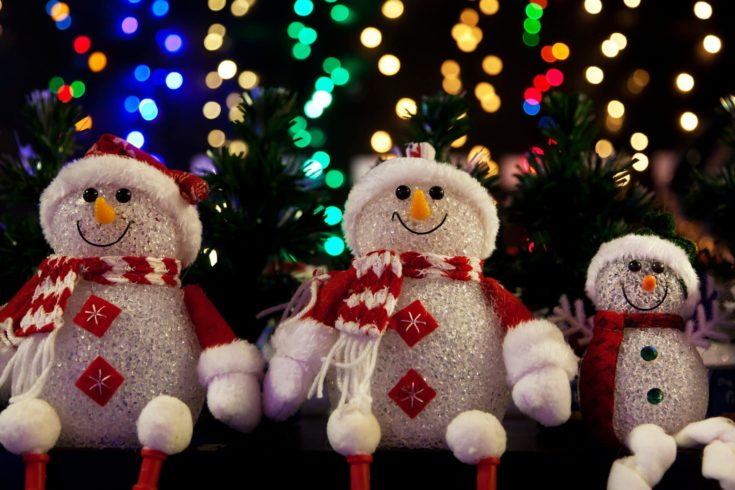 Three foam snowman designed with santa themed clothings hanged in christmas tree