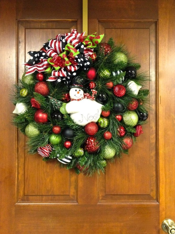 Christmas wreath hanged by the door with a snowman placed on the center of it