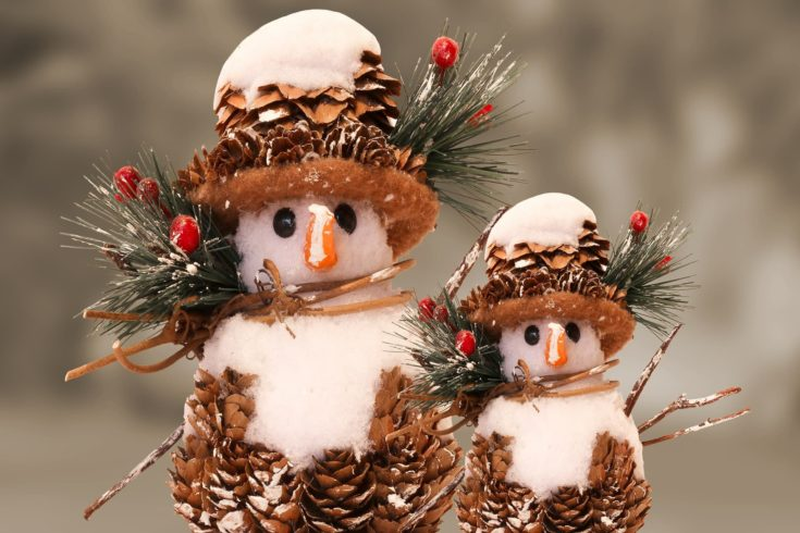Two little snowman with pinecones designed in its body and hat