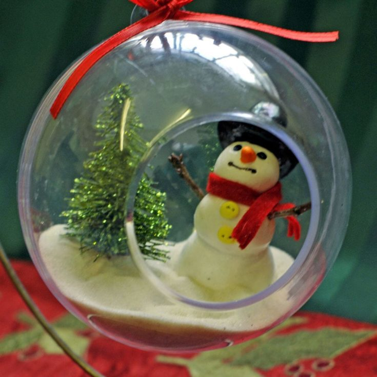 Little snowman and christmas tree placed inside a round transparent glass hanging