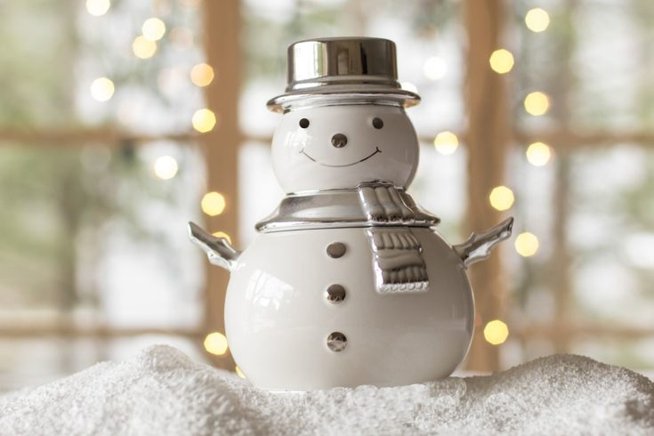 Snowman centerpiece placed on a white sand with blurred window glass on the background