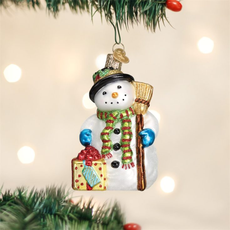 Cute little snowman holding broom and gift hanging on a christmas tree