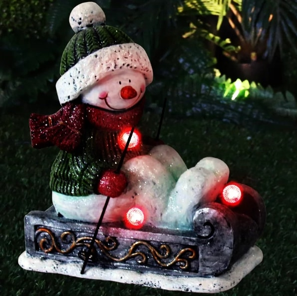 Snowman riding a sleigh with red lights on its neck, by the legs and under its feet