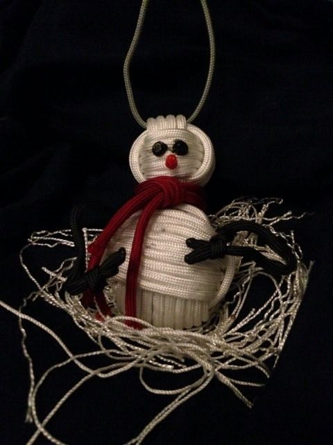 White cord strings formed as body of snowman and red cord string as scarf with two small eyes and red nose