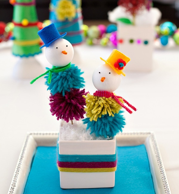 Two mini-snowman with pompom bodies with blue and orange hat on each