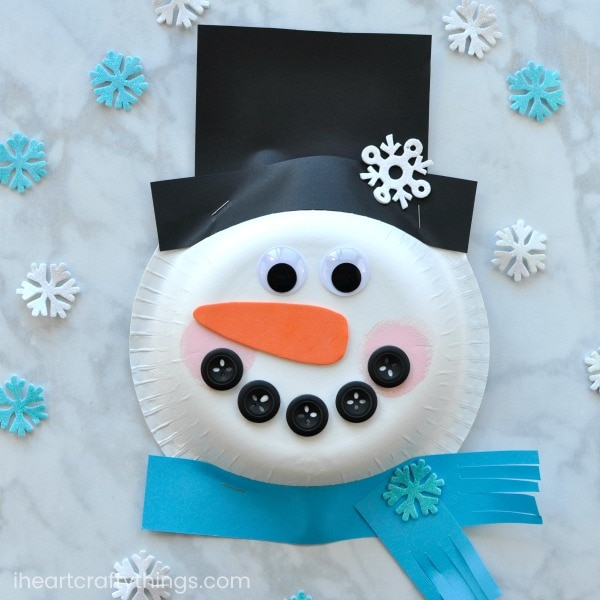 Paper plate with two googly eyes and five buttons forming a smile attached with orange paper as nose and black paper as hat surrounded with blue and white small snowflakes