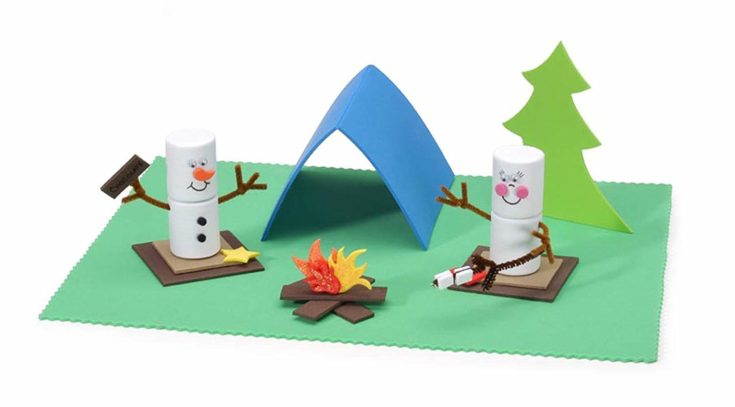 Two DIY snowman and a miniature bonfire with tent and pine tree in the background