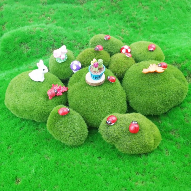 Assorted artificial moss rocks on a greenry ground with decorative red bugs,rabbit and flowers.