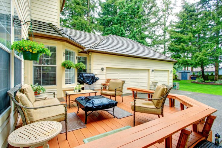 Luxury house backyard. View of walkout desk with patio table set and basketball court