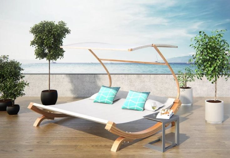Chaise lay back lounge with several indoor plants with view of sea on the background