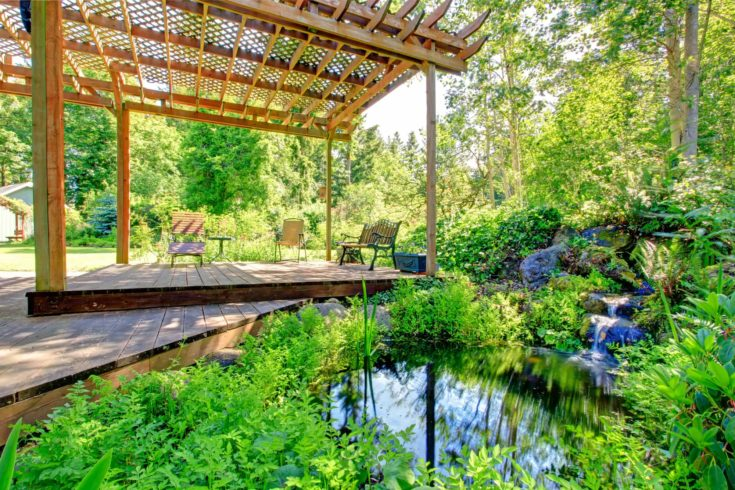 Big pergola with rustic chairs and bench open to beautiful small pond with little waterfall