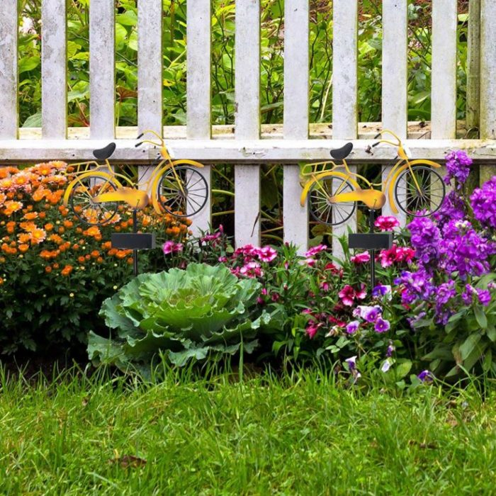 Two little yellow bikes on orange and purple flowers beside the fence