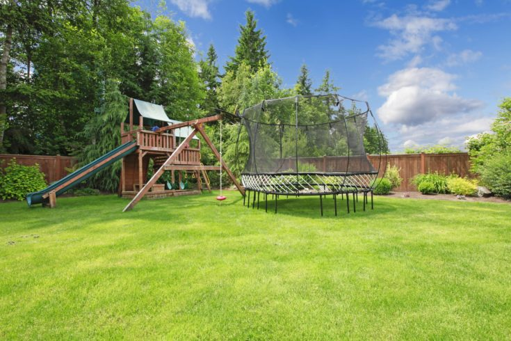 Play kinds ground area with trampoline and a slide in fenced backyard during summer.
