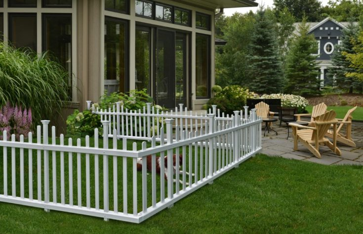 White dog fence outside an elegant house with patio on the background