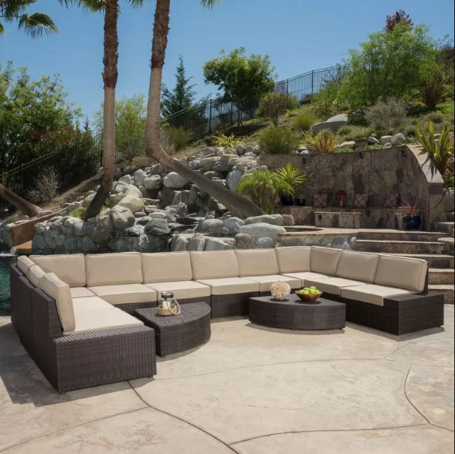 Rattan sectional set with cushions placed on a stoned walkway with bedrock on the background