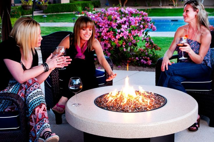 3 women in a rounded fire pit with flowers and modern swimming pool in the background