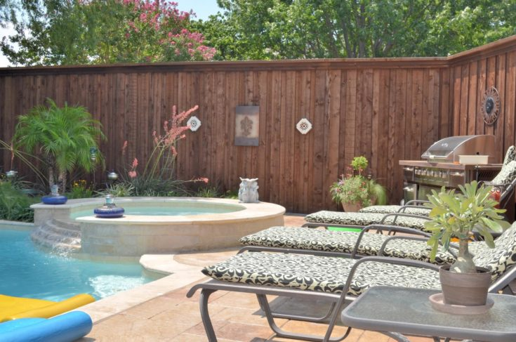 Beautiful deck beside pool in the suburbs, with grill, spa, and chaise lounges.