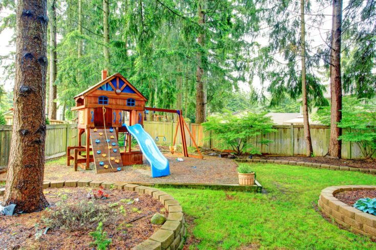 Fenced green backyard with playground for kids