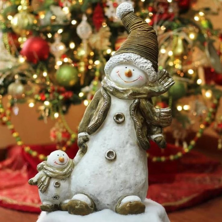 Cute smiling snowman holding miniature one with a blurred Christmas tree on the background
