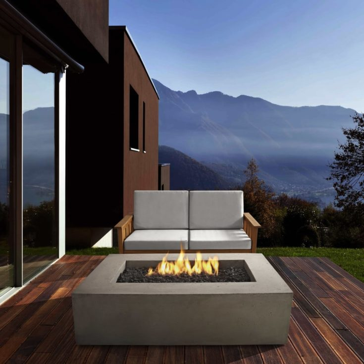 Luxury deck view of an elegant house with a fire pit and a mountainside view on the background