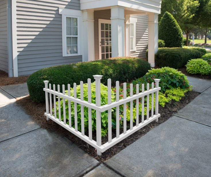 Sidewalk wooden white fence and bushes with a simple and elegant house on the background