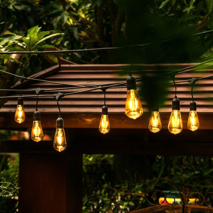 Overhanging light bulbs with a porch in the background