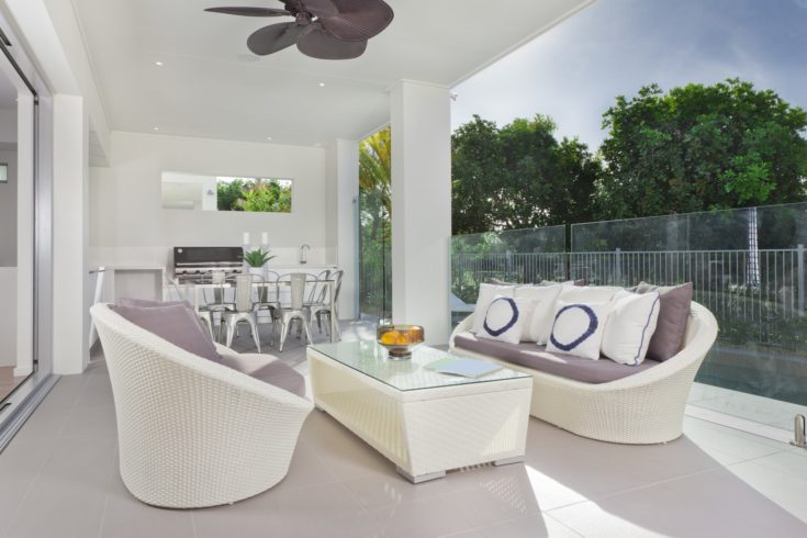 Luxurious undercover patio with couches, barbeque and dining area