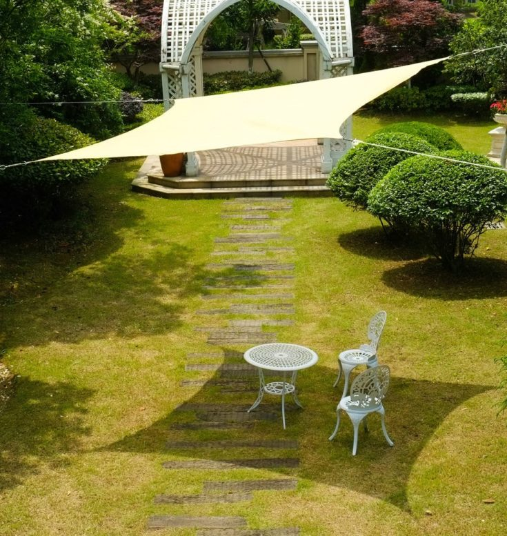 White steel chairs and table in the backyard garden with sail shade
