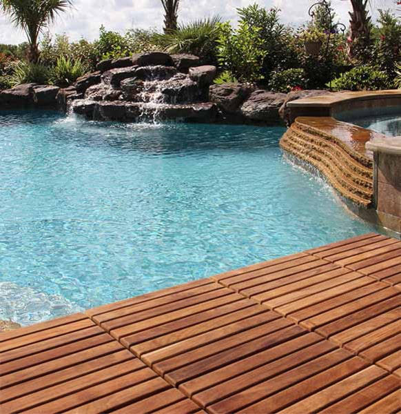 Modern swimming pool with a wooden deck and a magnificent rockscape