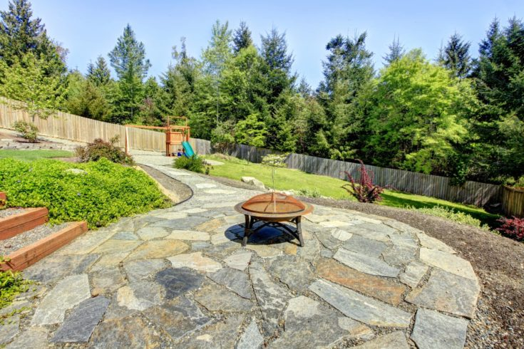 Large fenced backyard with stone and fire pit with trees.