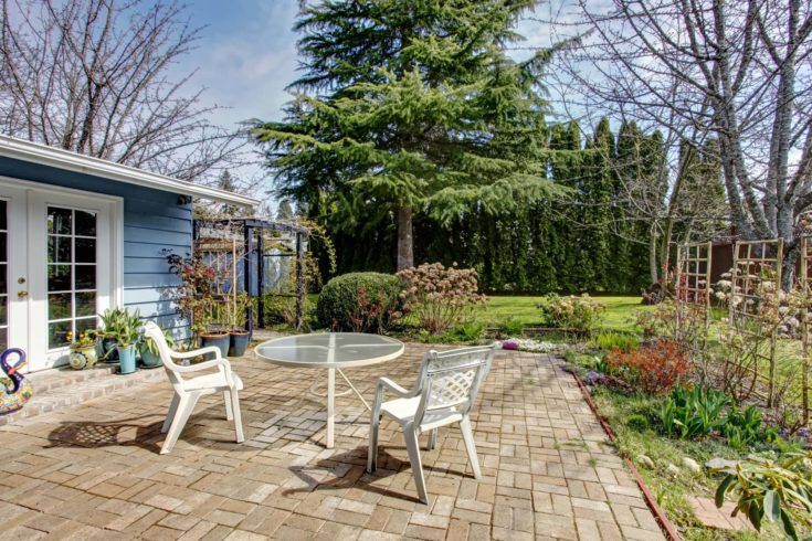 Brick floor patio area with table set. Area surrounded by flower bed with trellis