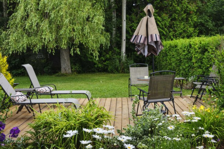 Wooden patio or deck in backyard of a home with outdoor furniture