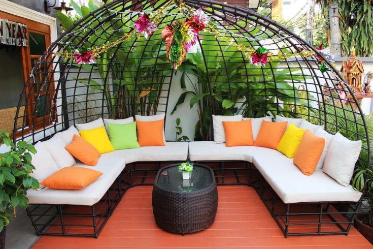 Rounded metal structure with several colorful cushions in a wooden backyard