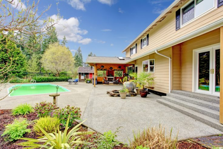 Concrete floor backyard with swimming pool, covered patio area and flower bed