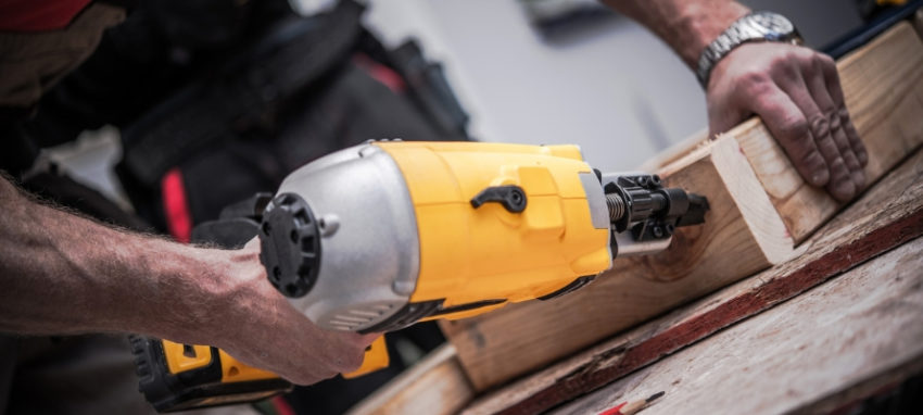 Caucasian Construction Worker Creating Wood Elements Using Powerful Nail Gun Tool